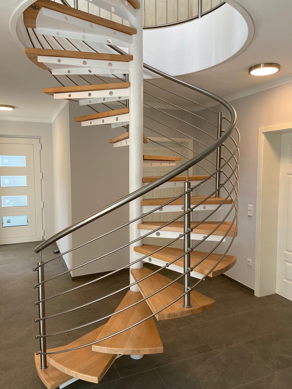 Spindeltreppe in weiß mit Stufen in Eiche natur und Treppengeländer in Edelstahl mit mitlaufenden Stäben