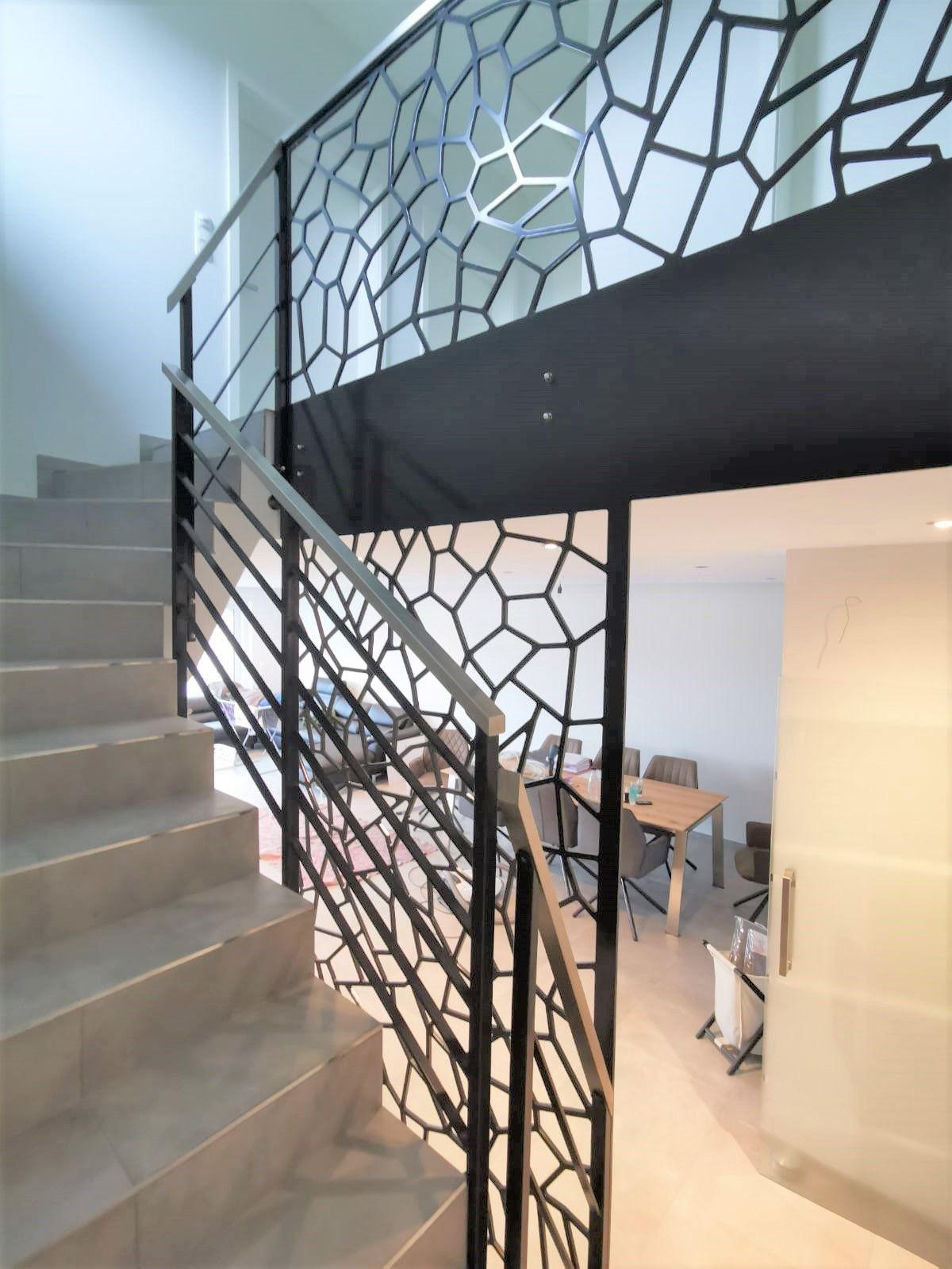 Treppengeländer mit mitlaufenden Flachstäben in anthrazit und Edelstahlhandlauf, Brüstung im Camouflage-Stil